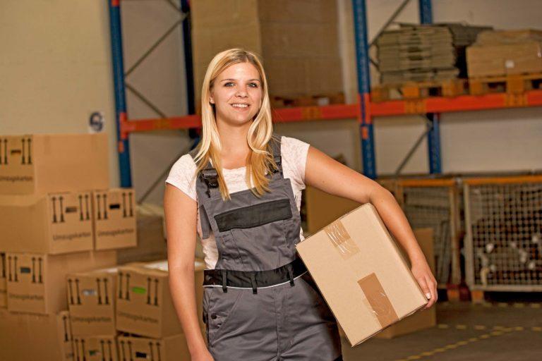 bbw-Auszubildende im bbw Südhessen in Lagerhalle mit Paket unterm Arm