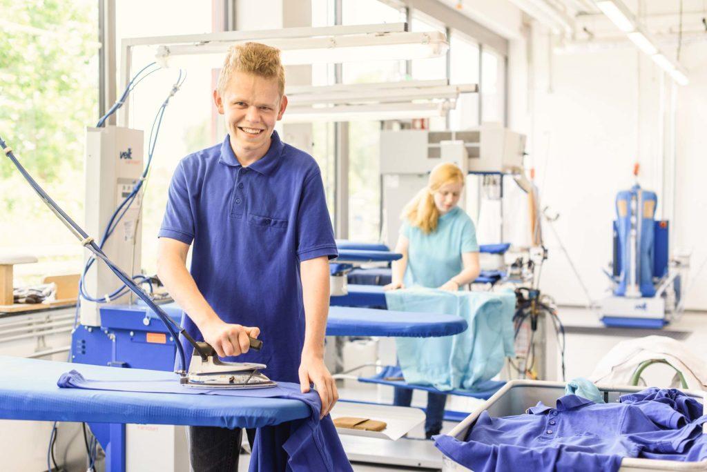 In der bbw Südhessen Textilreinigung arbeiten junge Frauen und auch junge Männer. Hier sehen sie bbw-Azubis am Bügelbrett..