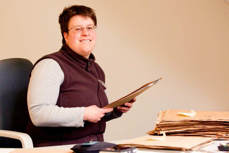 Bürokauffrau sitzt am Schreibtisch und hält Akten in der Hand