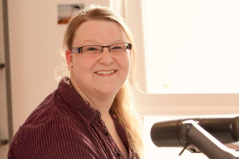 Frau sitzt am Schreibtisch in Büro - eine Bürokauffrau