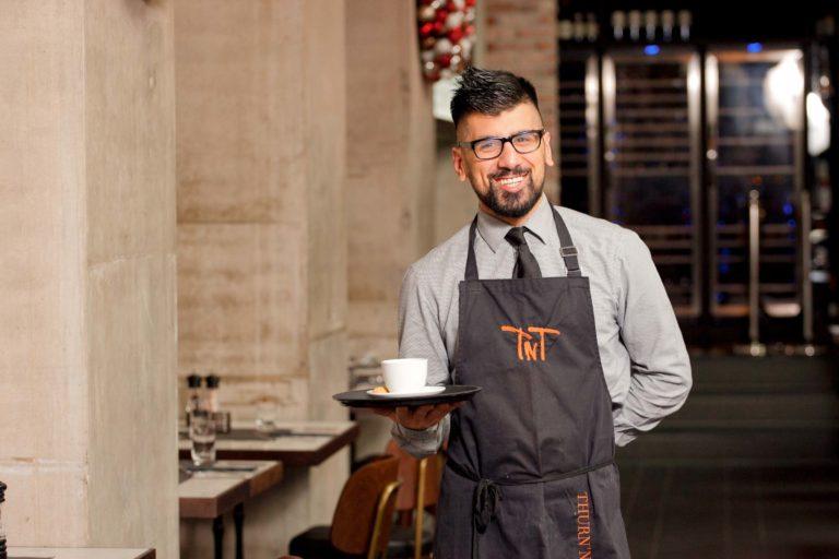 Mann aus dem Gastro-Gewerbe mit Tasse in der Hand