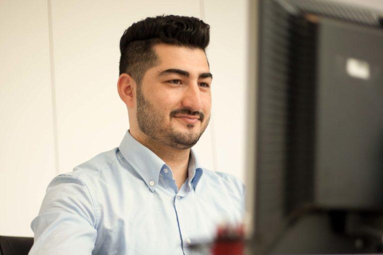ausgelernter Industriekaufmann sitzt am Rechner und arbeitet in seinem neuen Job