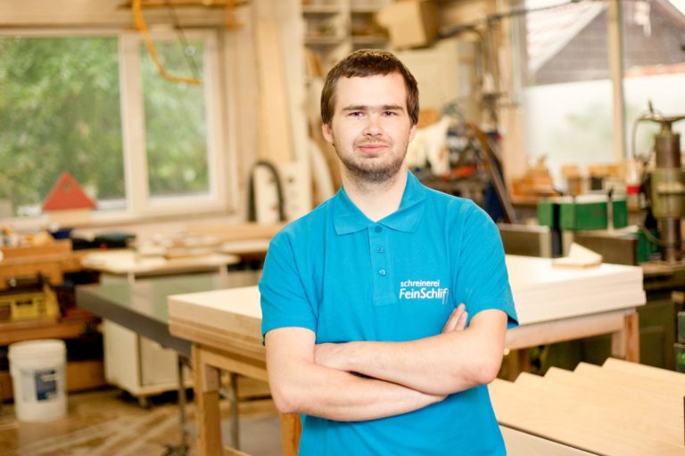 Junger Mann vor einem Tisch in der Holzwerkstatt