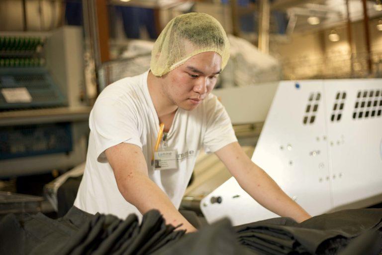 Auszubildender an Mangel-Maschine in der Textilreinigung
