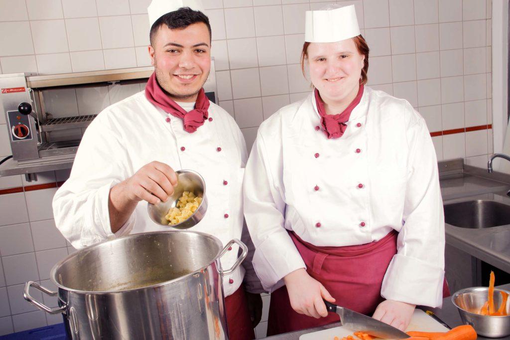 zwei Köche-Azubis aus dem Berufsbildungswerk Südhessen stehen gemeinsam am Kochtopf in der Ausbildungsküche