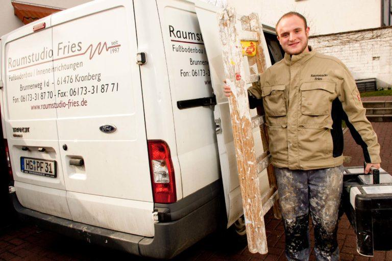 Junger Mann steht mit Leiter ausgerüstet an einem Firmenwagen-Bodenleger