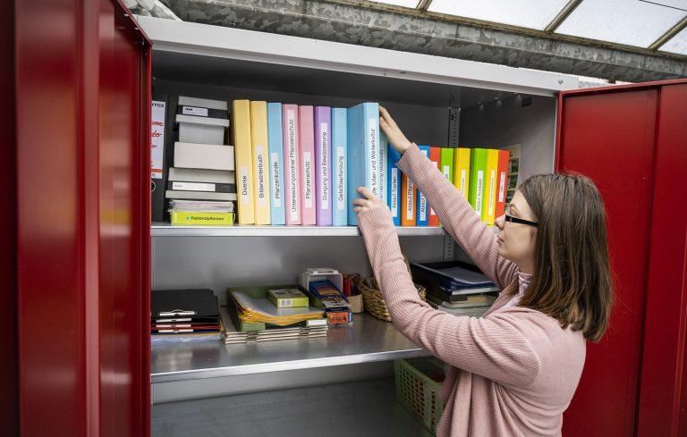 Junge Frau aus dem Autismus-Spektrum nimmt sich einen Ordner aus einen nach Farben gut sortiertem Schrank.
