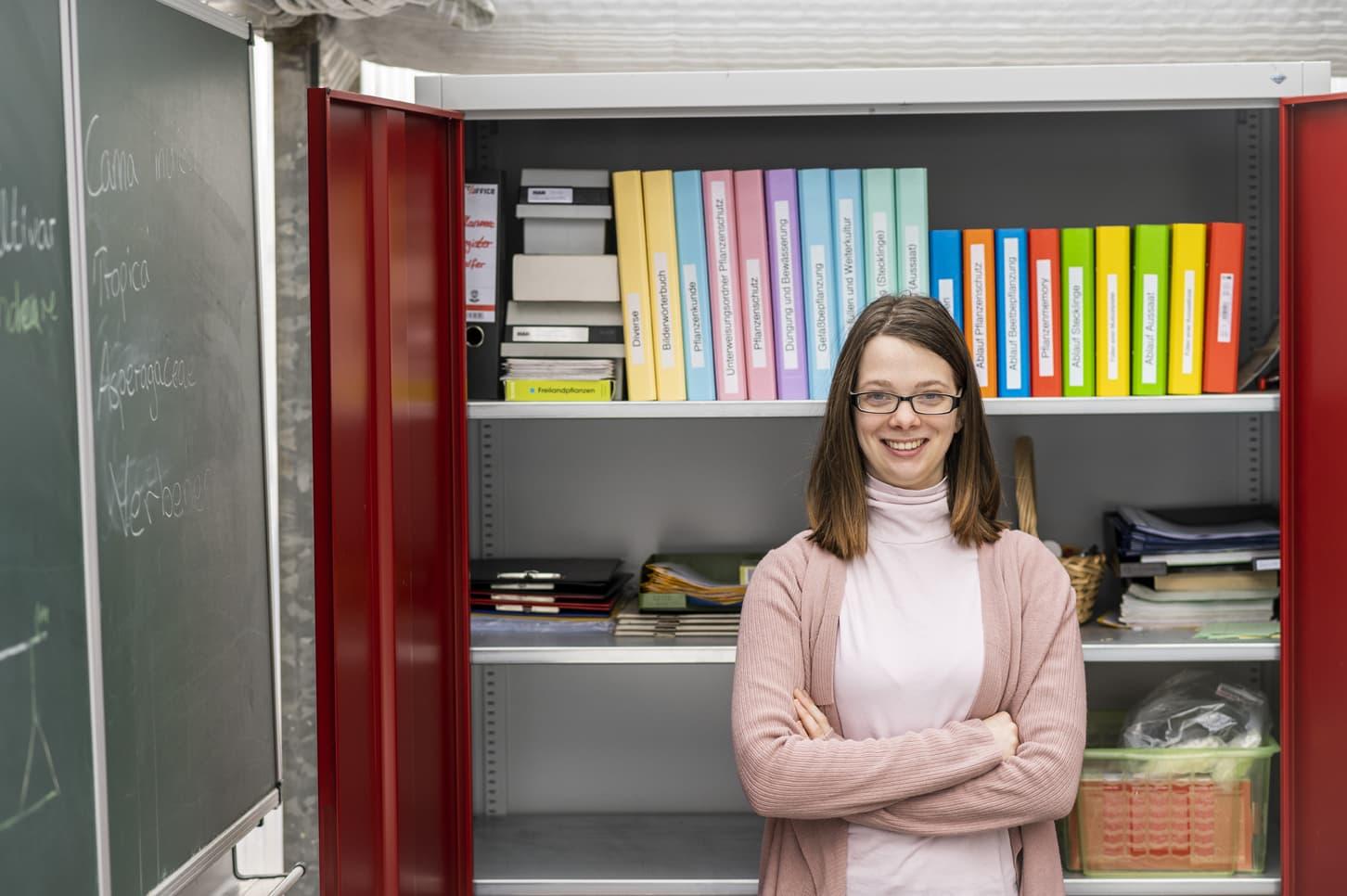 Junge Frau vor aufgeräumten Schrank mit nach Farben sortierten Ordnern