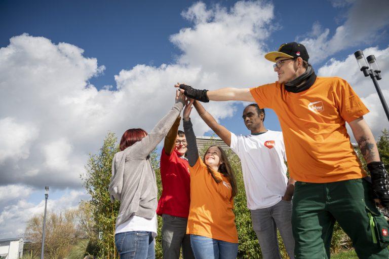 Gruppe junger Menschen von unten nach oben fotografiert beim high five geben