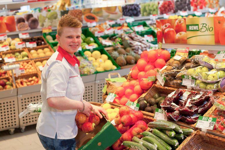 Ehemaliger Azubi am Gemüseverkaufsstand im Supermarkt