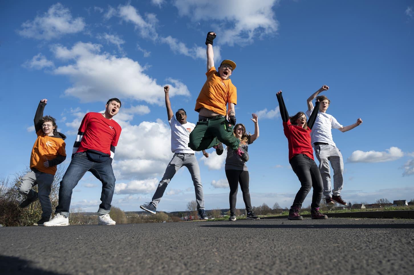Gruppe Jugendlicher springt vor blauem Himmel in die Höhe