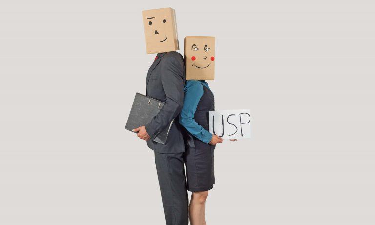 neue akademie: Seminare & Beratung im bbw Südhessen. Mann und Frau Rücken an Rücken. Mann hält Mappe in der Hand, Frau hält Schild in der Hand auf dem USP steht.
