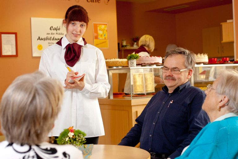 Junge Frau, die an einem Tisch im Kaffee die Bestellung der Gäste aufnimmt