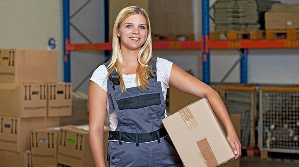 bbw Südhessen Auszubildende in der Lagerlogistik steht mit Paket unterm Arm vor einem Lagerregal