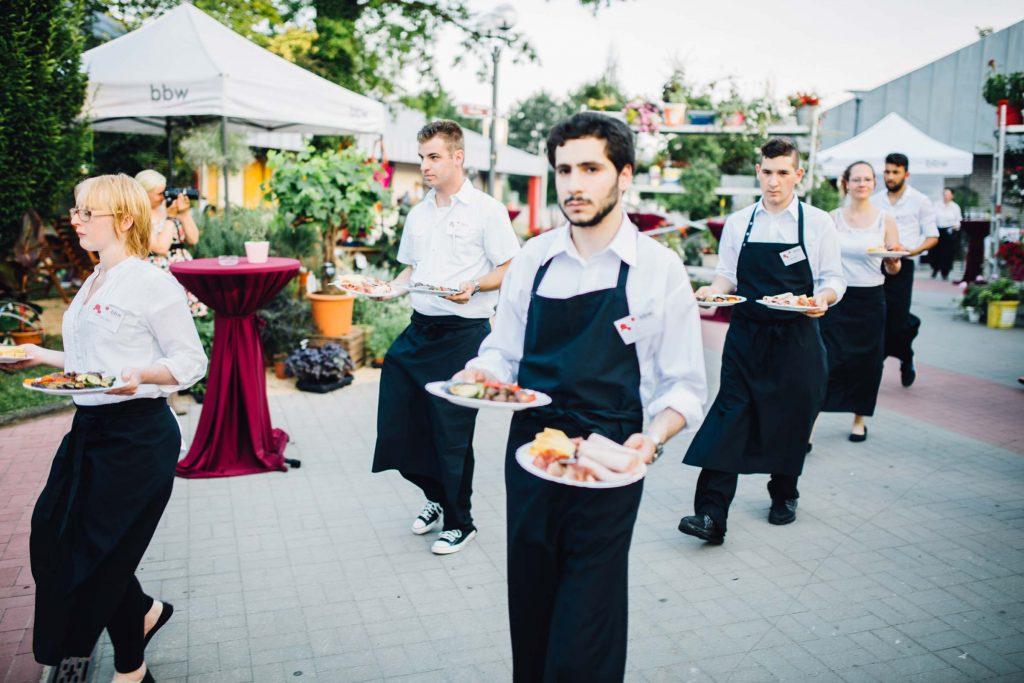 Teilnehmer*innen fon fair & lecker, unserem Cateringservice, servieren gerade auf einer Feier.