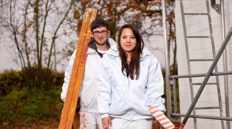 Junge und Mädchen stehen neben Malergerüst. Er trägt eine Leiter, sie eine Malerrolle.