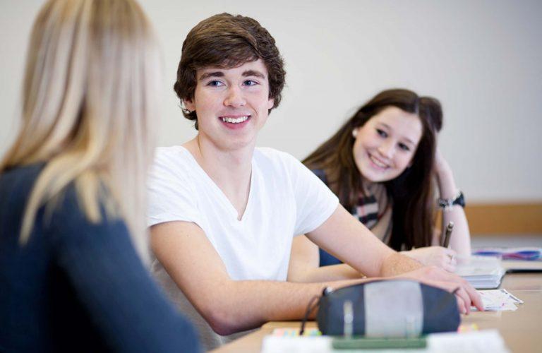 Schüler*innen sitzen an einem Tisch. Sie gehören dem Projekt Berufseinstiegsbegleitung im bbw Südhessen an
