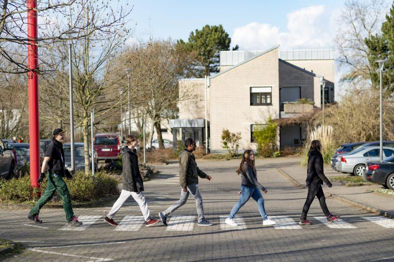Gruppe Jugendliche marschiert wie die Beatles über die Abbey Road hintereinander über Zebrastreifen in das Berufsbildungswerk
