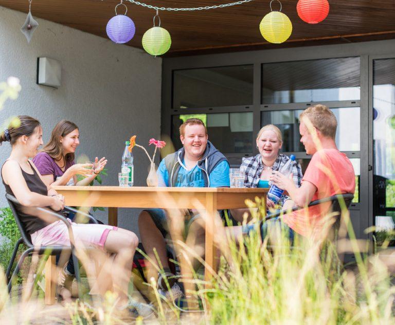 Gruppe Jugendliche sitzt am Tisch auf Terrasse und redet und lacht