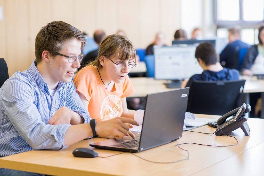 bbw Südhessen Azubis der Kaufleute vor dem Laptop sitzend am Schreibtisch