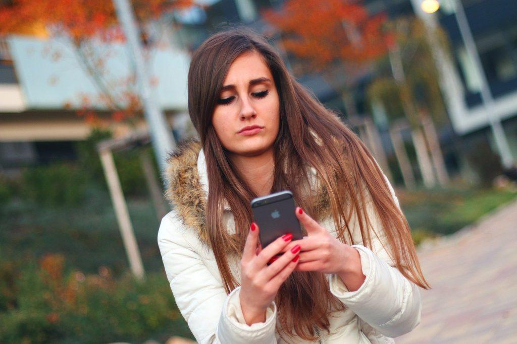Junges Mädchen nimmt Kontakt per Handy Kontakt zum Berufsbildungswerk Südhessen auf
