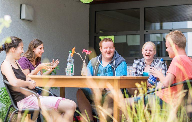 Gruppe Jugendliche sitzt auf Terrasse an einem Tisch und reden und lachen