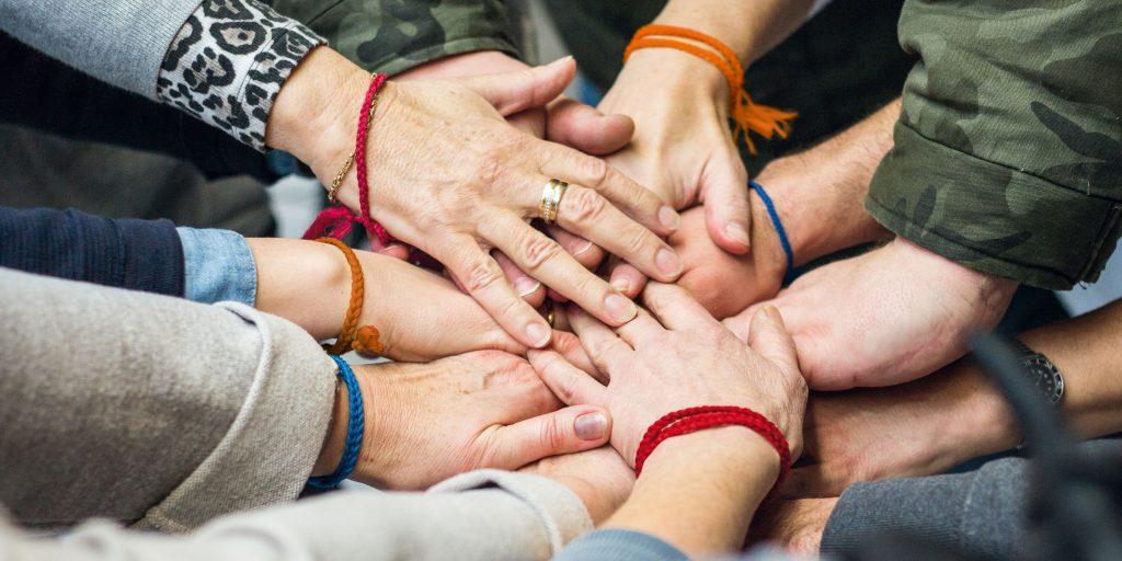 Von allen Seiten werden Hände in die Bildmitte gestreckt, die übereinander gestapelt gehalten werden