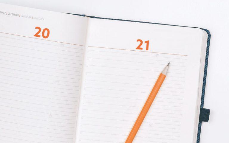 Aufgeschlagener Kalender mit orangenem Bleistift oben drauf.