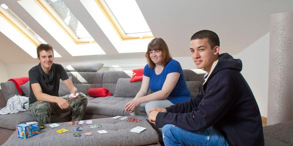 Drei junge Teilnehmer sitzen auf einem Ecksofa und spielen Karten