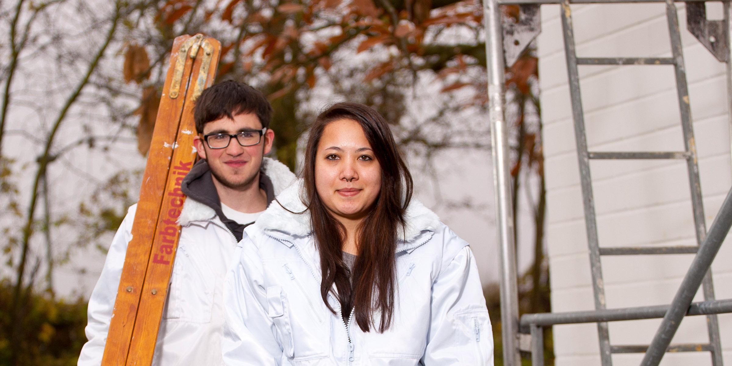 Zwei Maler-Azubis aus dem Berufsbildungswerk Südhessen, männlich und weiblich, des bbw Südhessen in Maler-Arbeitskleidung mit Leiter und Malerrolle ausgestattet