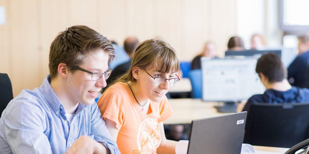 Zwei Auszubildende sitzen am Schreibtisch im Ausbildungsraum und arbeiten am Laptop