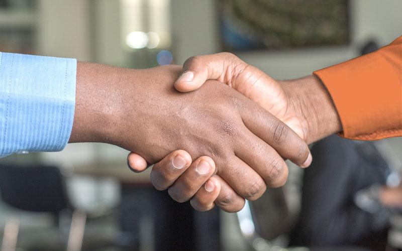 Foto von zwei Händen, die sich zum Handshake in der Bildmitte treffen