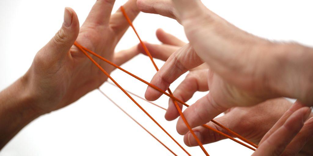 Hände spinnen ein Netzt aus Wolle - bbw-suedhessen-berufsbildungswerk-netzwerk