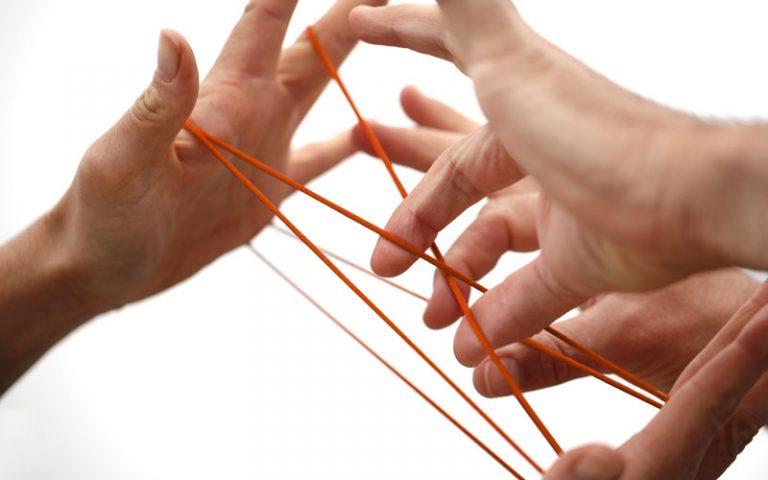 Vier Hände spielen mit einem orangenen Faden