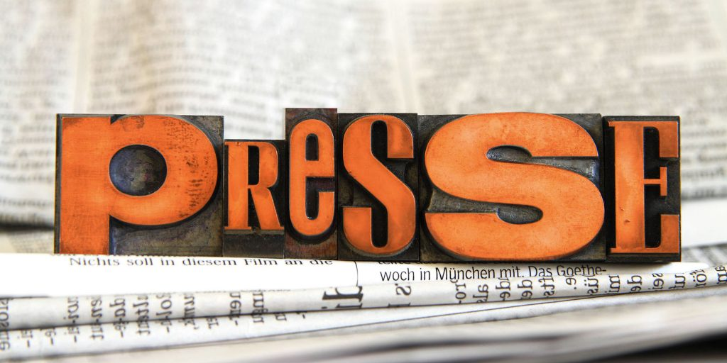 """Punzen, die """"Presse"""" bilden in verschiedenen Schriftarten, auf einem Stapel Zeitungen"""