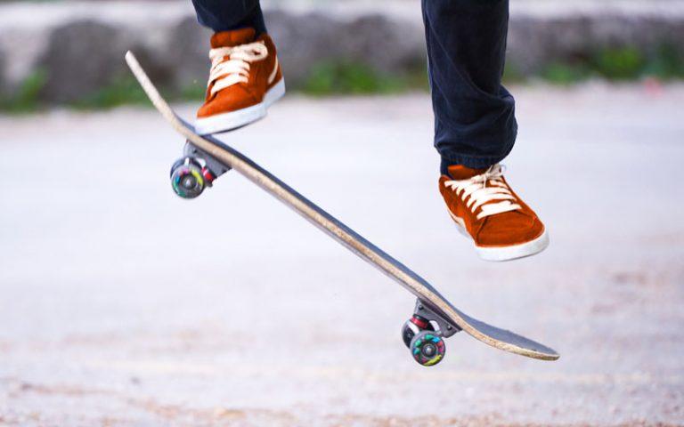Beine mit orangenen Turnschuhen, darunter ein Skateboard. Der Skateboardfahrer macht gerade einen Sprung