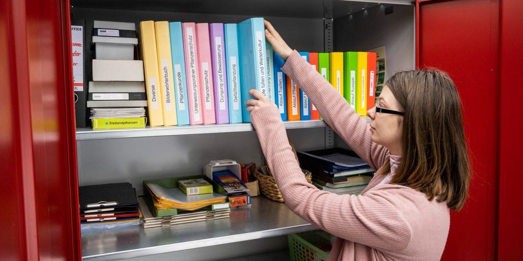 bbw Südhessen-spezielle Anbebote für Autisten: unge Frau sortiert einen blauen Ordner der passenden Farbe im Schrank hinzu.