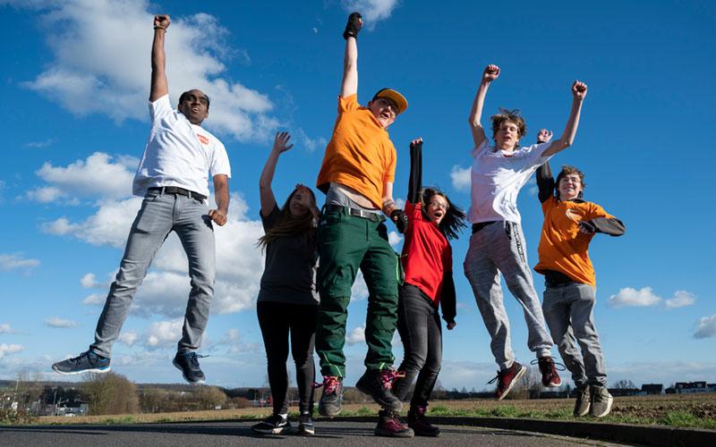 Junge Menschen in bunten T-Shirts springen in die Luft
