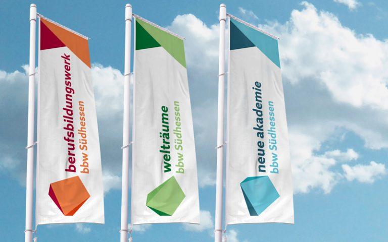 Drei Fahnen mit bbw Motiven (berufsbildungwerk, welträume und neue akademie) vor blauem Himmel mit weißen Wolken