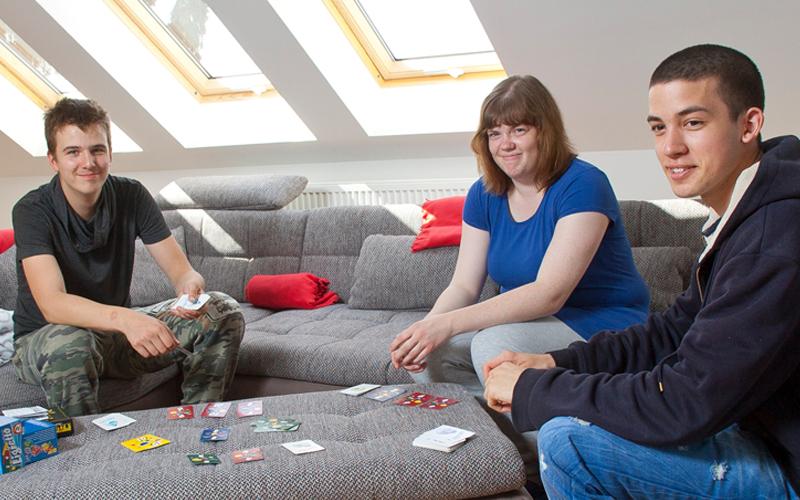 Drei Jugendliche sitzen auf der Couch und spielen Karten