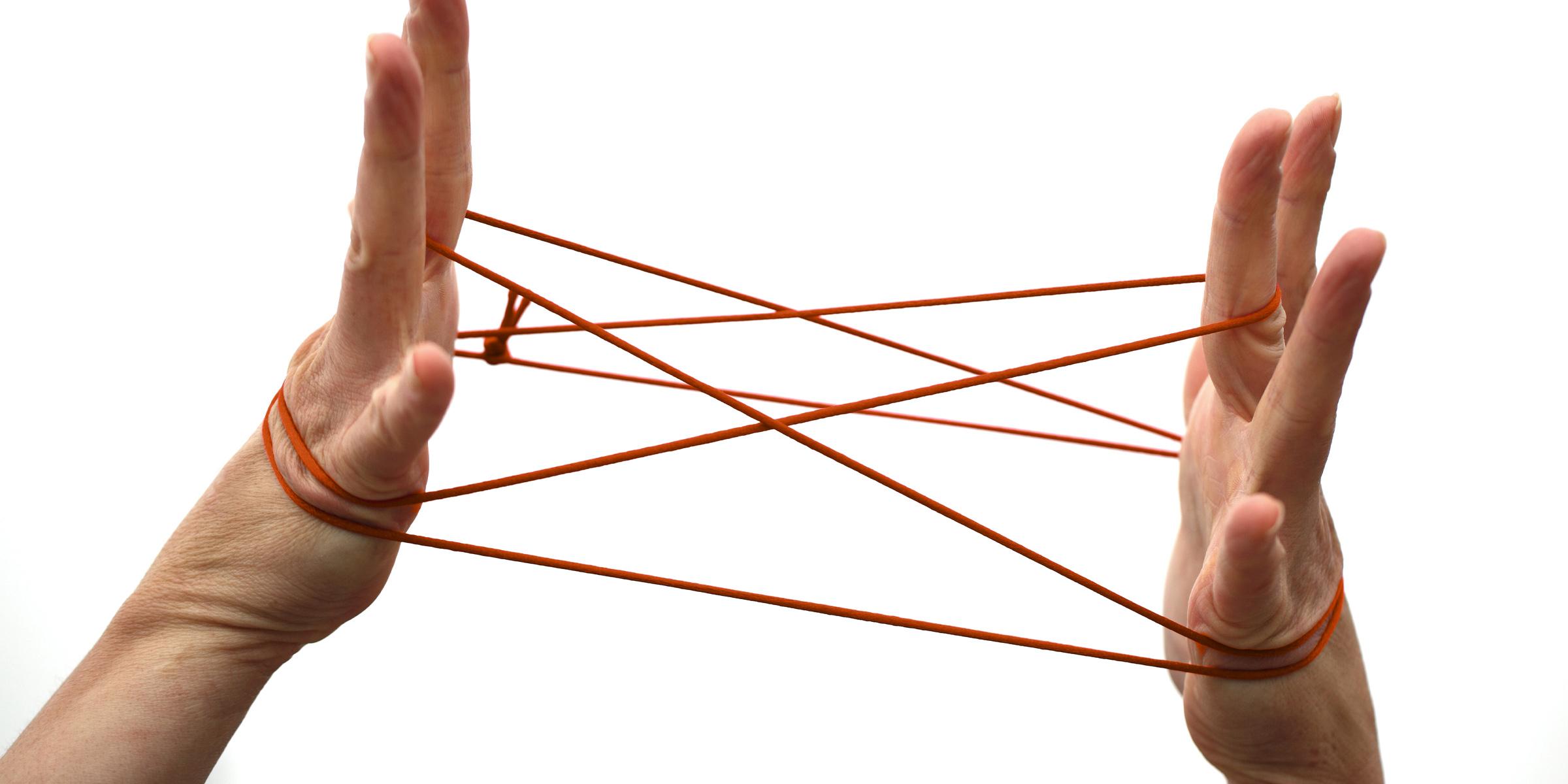 Zwei Hände spielen mit Fäden