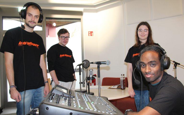 Vier junge Teilnehmer sitzen und stehen um ein Tonmischpult herum und schauen in die Kamera