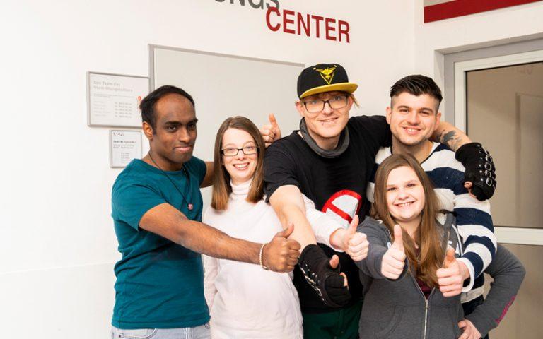 Teilnehmende stehen in einer Gruppe zusammen, lachen in die Kamera und zeigen den Daumen hoch. Im Hintergrund ist die Tür zum Vermittlungscenter