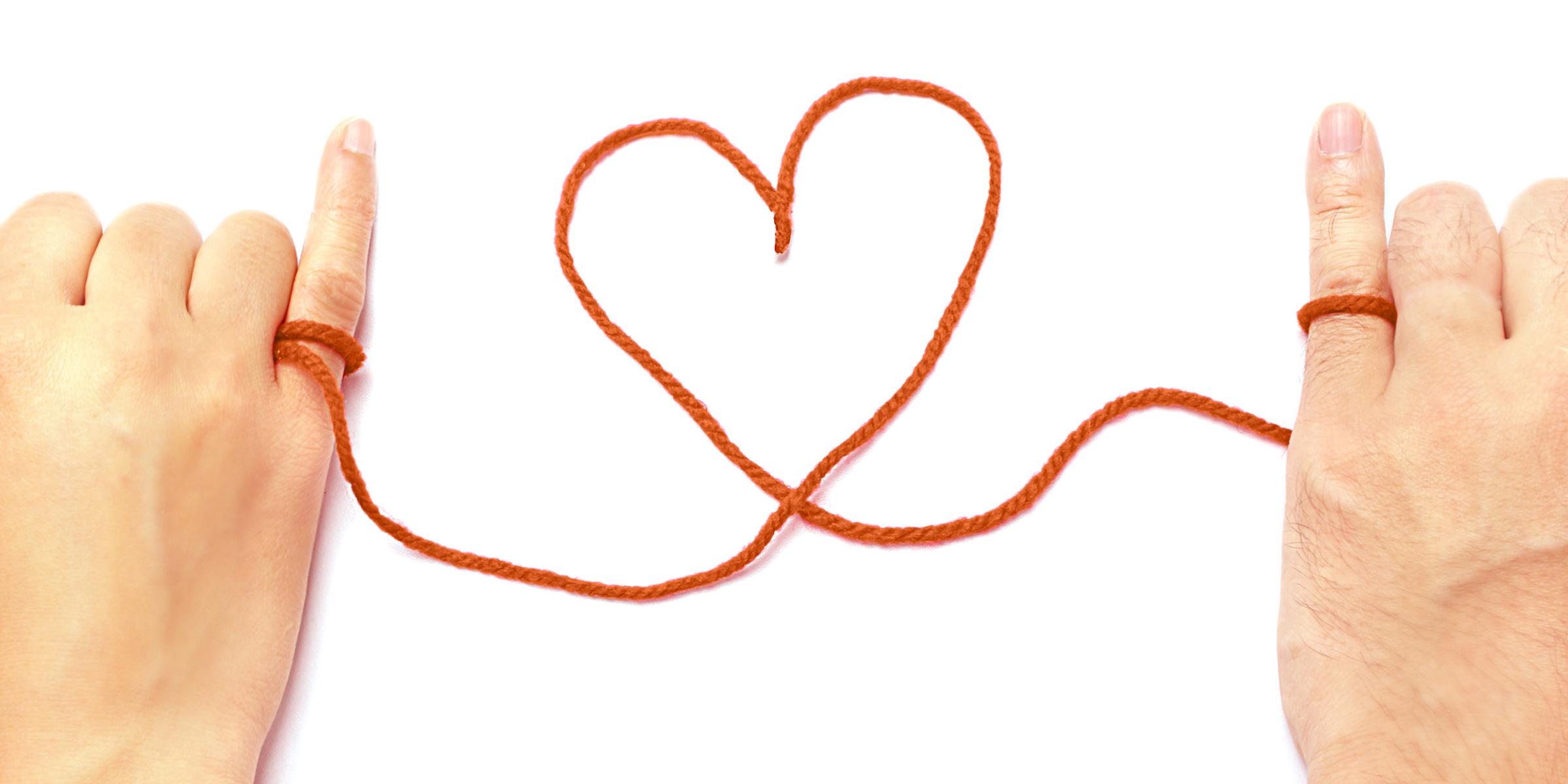 Zwei Hände, in der Mitte liegt ein Herz gebildet aus Faden. Die Enden sind um die Finger der Hände gewickelt