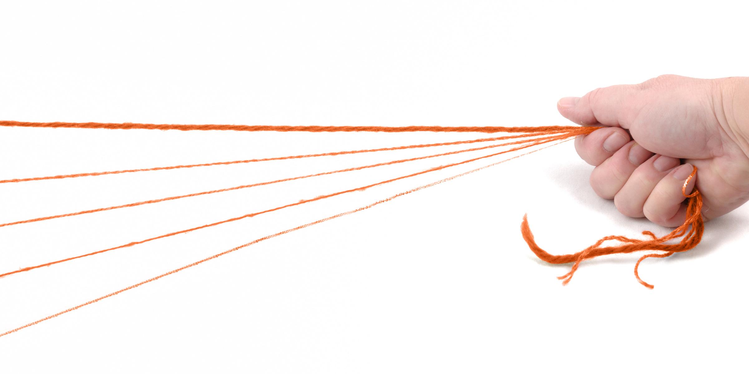 Fäden, die in einer Hand zusammenlaufen