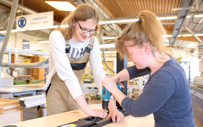 Zwei Auszubildende bearbeiten ein Stück Holz