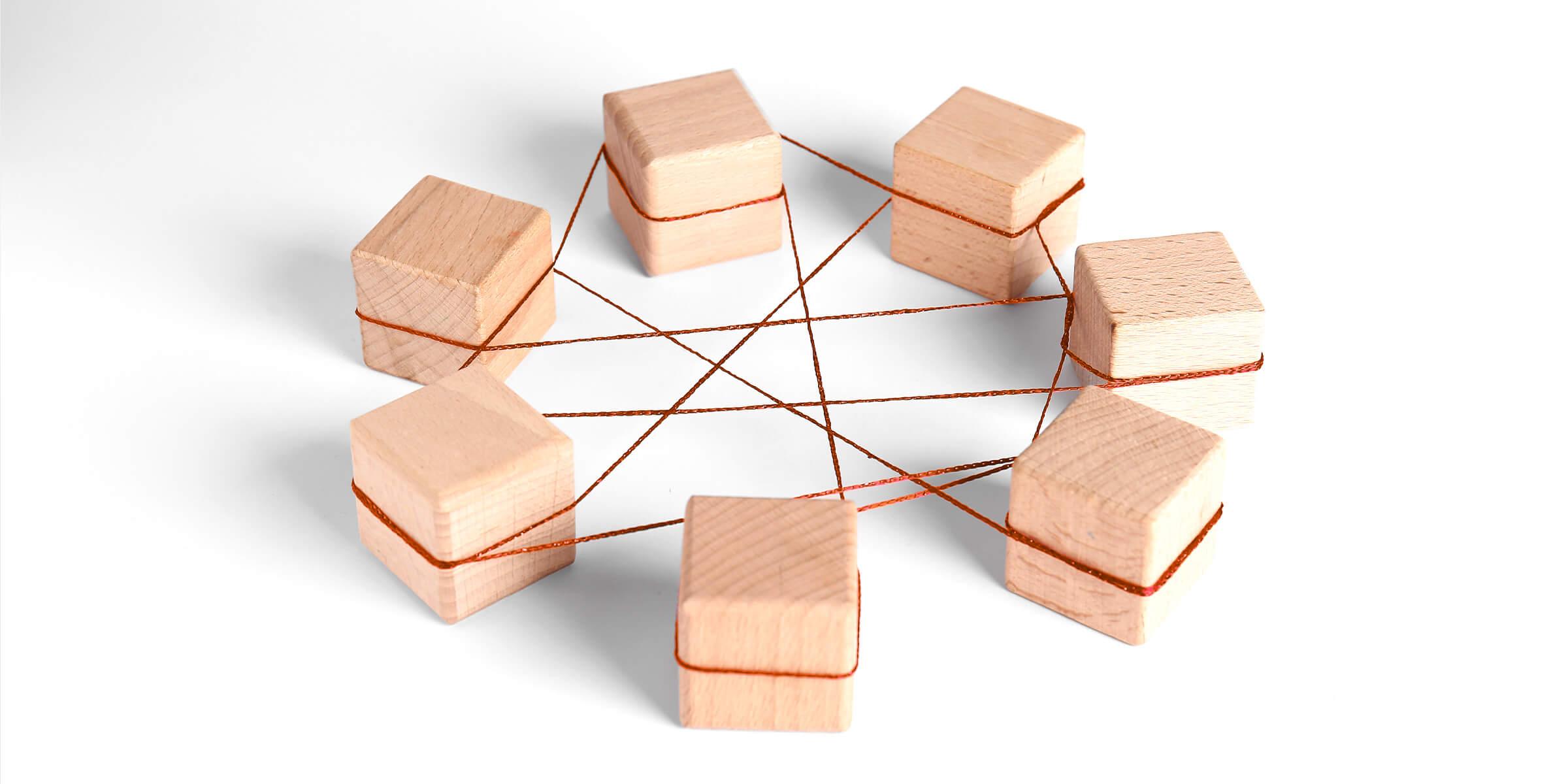 Holzklötze mit orangenen Fäden verbunden