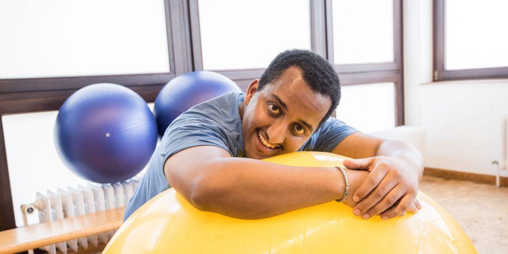 Individuelle Reha-Förderung im bbw Südhessen: Teilnehmer liegt mit dem Oberkörper auf einem Gymnastikball und lächelt in die Kamera
