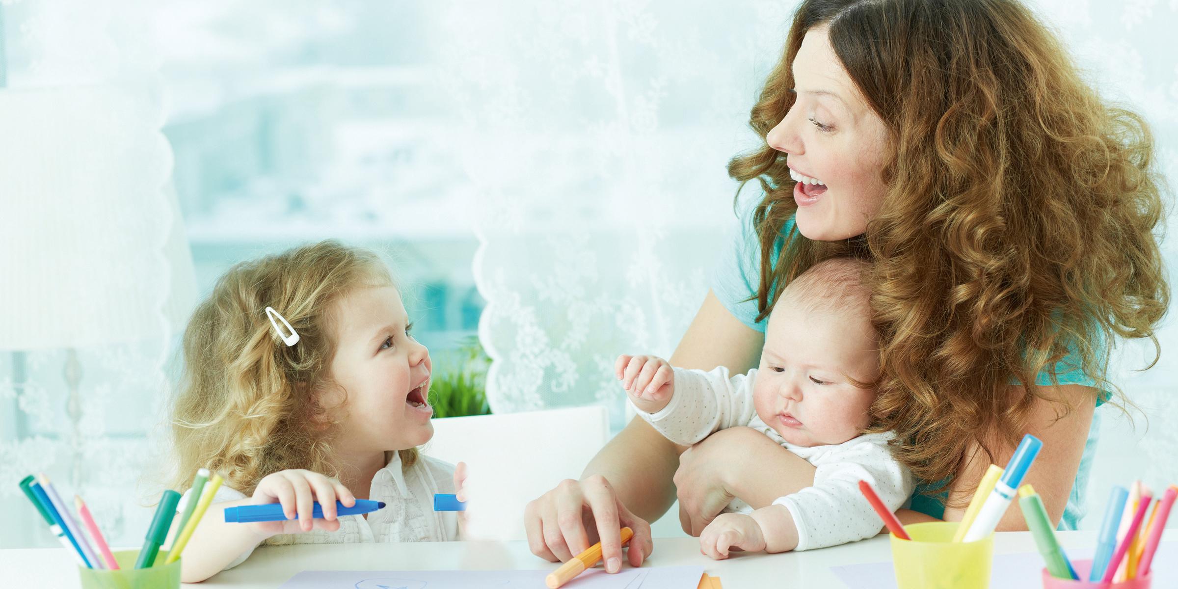Frau mit Baby auf dem Arm lacht ein zweites Kleinkind an