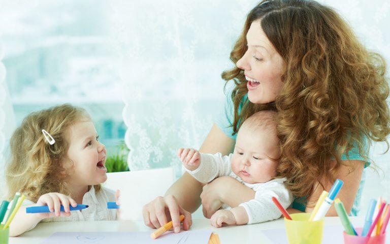 Mutter mit Baby auf dem Arm lächelt ein zweites Kind an